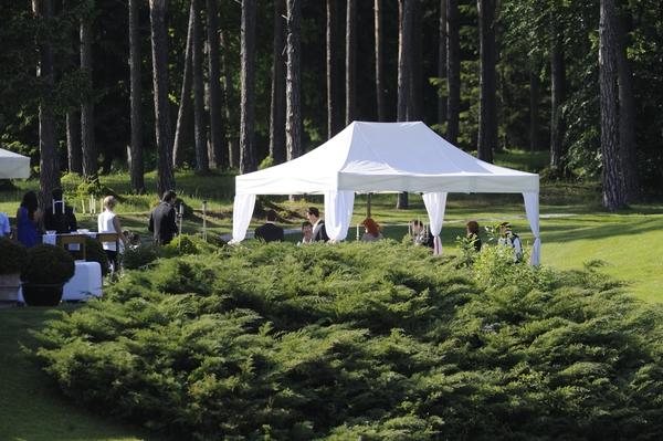 Poročni obred je potekal na prostem, pod belim šotorom.