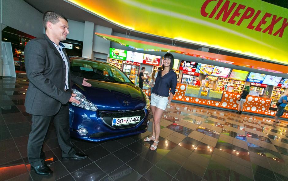 Predstavnik blagovne znamke Peugeot Adam Kavšek predaja ključe vozila Peugeot 208 Active srečni nagrajenki Kaji Lozar (foto: Foto: Jernej Kogelnik)