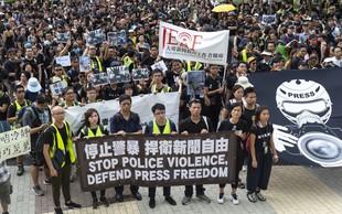V Hongkongu moški v belih majicah in s palicami huje pretepli demonstrante