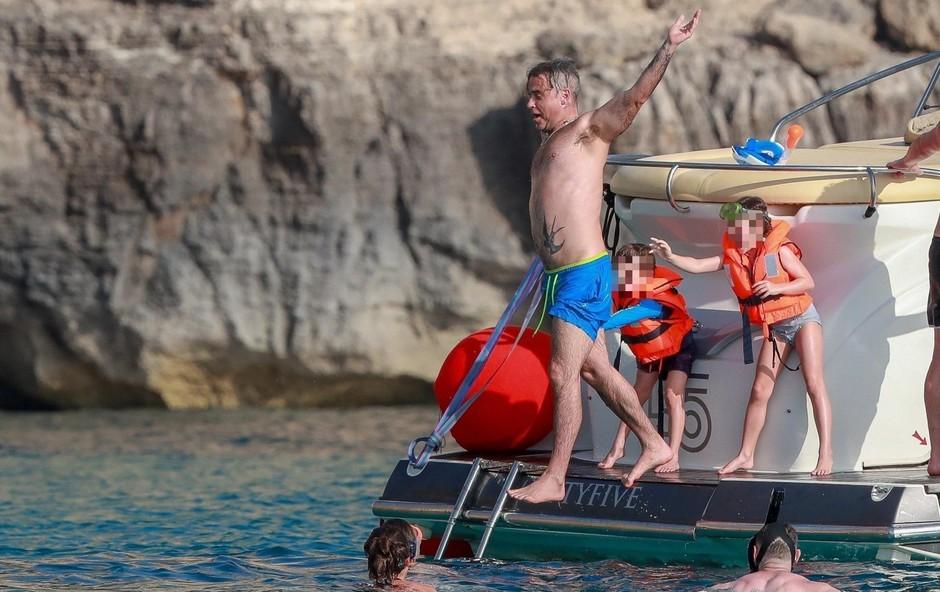 Družina s prijatelji biva na jahti, Robbie pa najbolj uživa pri igri z otroki. (foto: Profimedia)