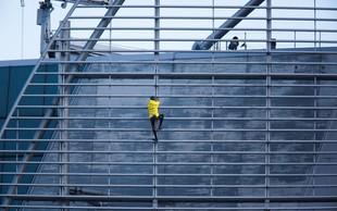 """""""Francoski spiderman"""" na stolpnico v Hongkongu splezal z zastavo miru"""