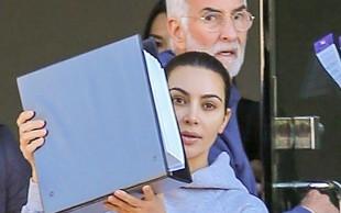 Kim Kardashian so paparaci ujeli povsem brez ličil, ko je hitela v avto in se skrivala za mapo