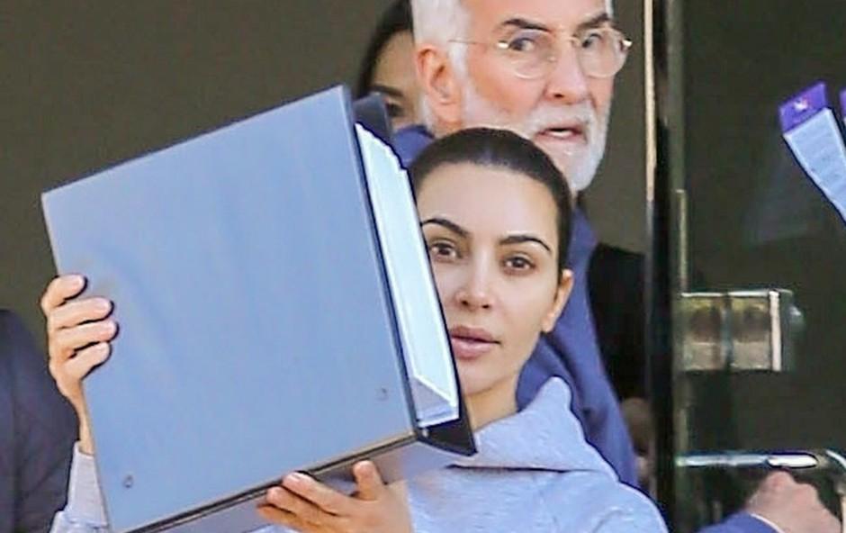Kim Kardashian so paparaci ujeli povsem brez ličil, ko je hitela v avto in se skrivala za mapo (foto: Profimedia)